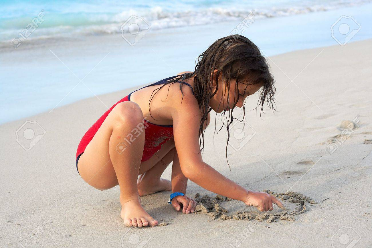 Beautiful caucasian girl writing in the sand with her finger Stock Photo - 5559543