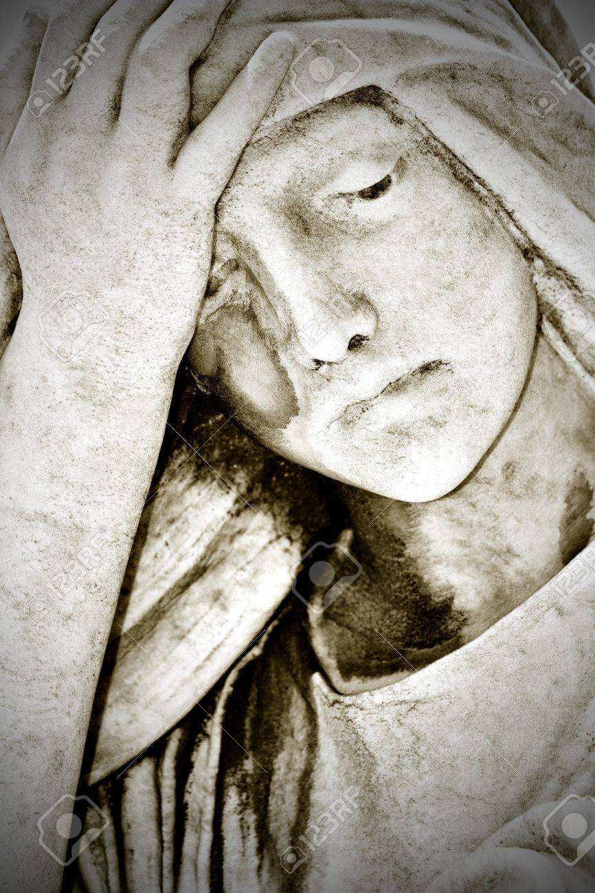 Close up of an old grunge statue representing a suffering young woman with a hand in her forehead Stock Photo - 10437373