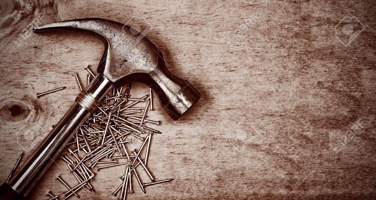Hammer and nails over a wood panel with space for text in dark sepia shades Stock Photo - 10437195