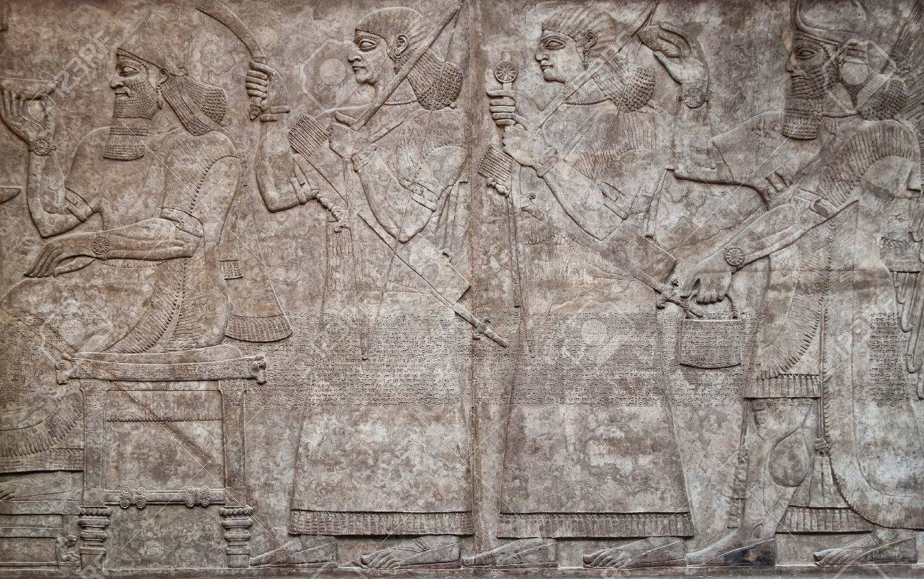Ancient assyrian clay relief depicting a row of warriors with weapons and text written in cuneiform writing - 10437196