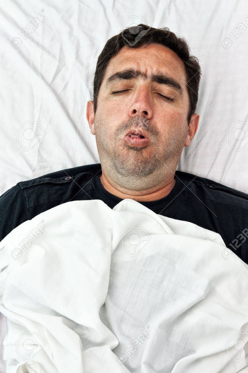 Portrait of a sick hispanic man laying in bed and coughing Stock Photo - 12156430