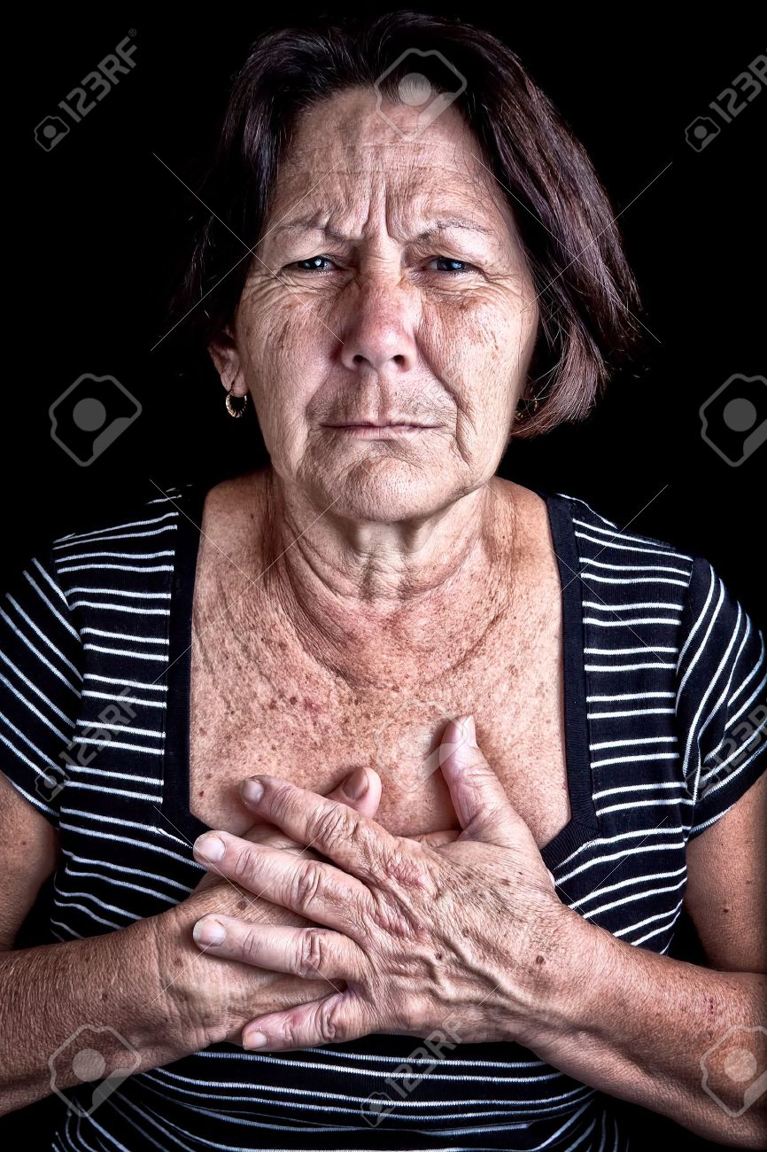 Mature woman suffering from chest pain or depression on a black background Stock Photo - 12748211
