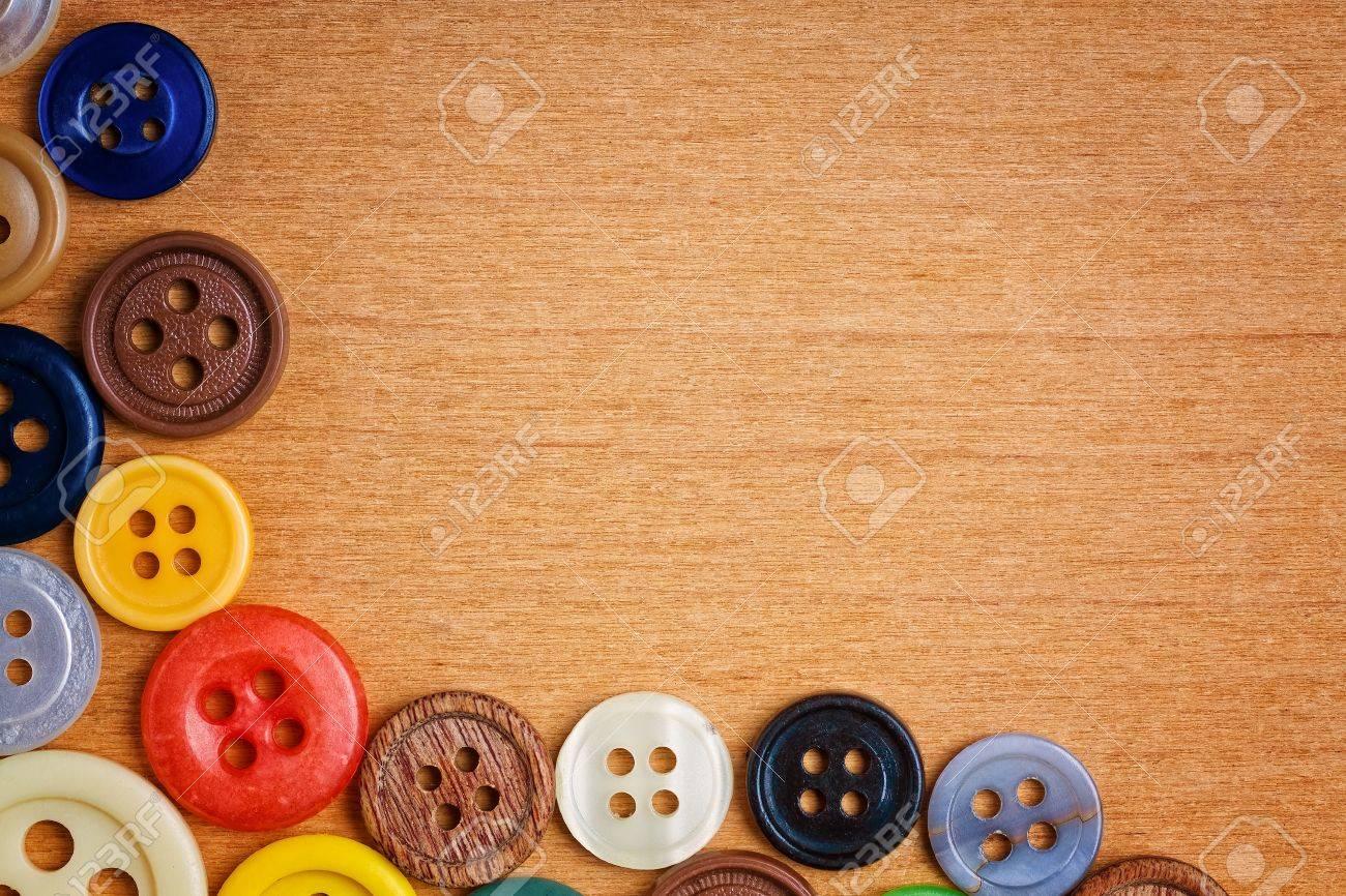 Coser los botones coloridos creando un marco en un fondo de madera con espacio para texto Foto de archivo - 12748224