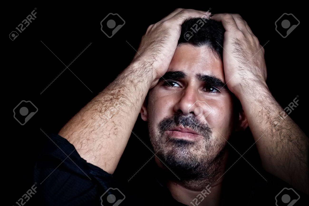 Portrait of a stressed and sad young man with a dramatic expression on a black background Stock Photo - 12748285