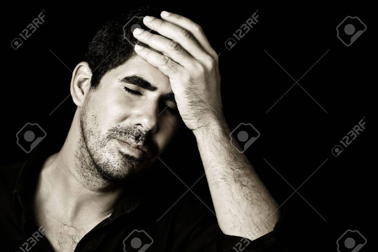 834de72d335cd5 Monochromatisch beeld van een jonge knappe bezorgd latino man of met een  hoofdpijn geïsoleerd op zwart