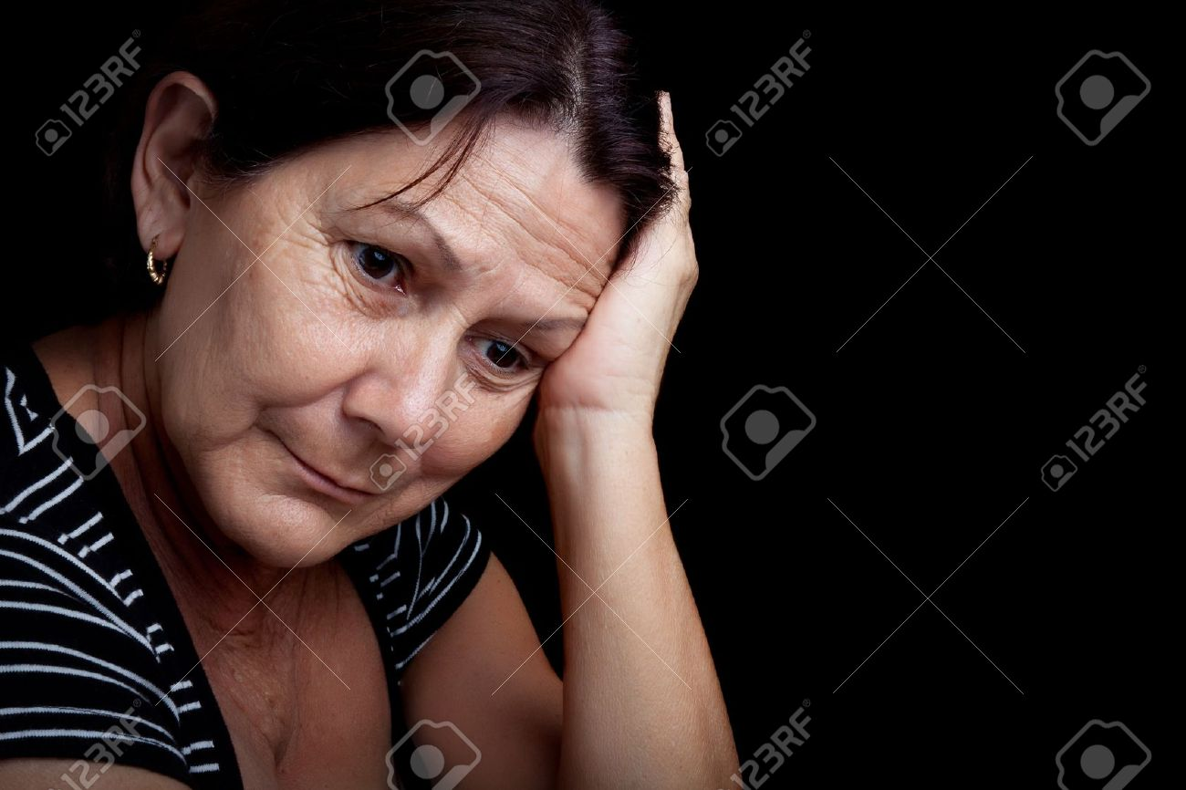 Portrait of a very sad and depressed older woman suffering from stress or a strong headache isolated on black - 12902914