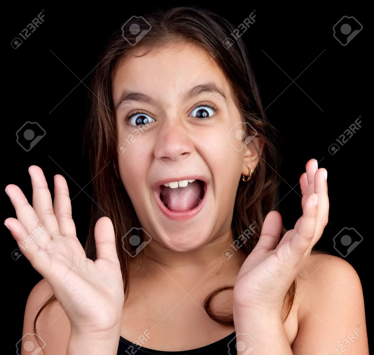 Portrait of a very surprised or scared girl screaming loudly on a black background Stock Photo - 13162522