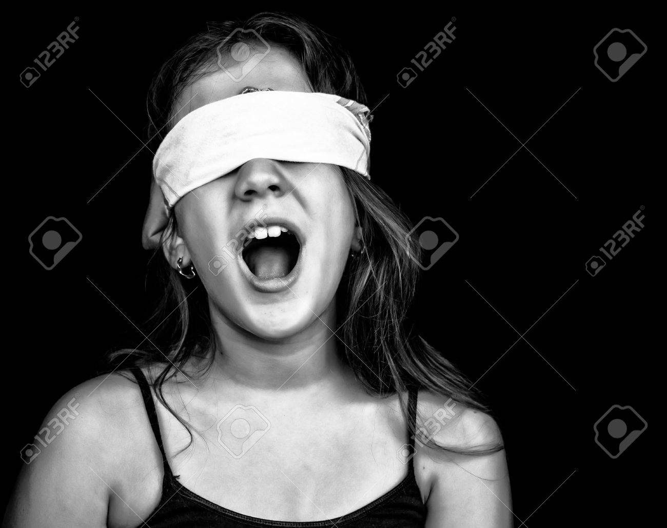 Black and white image of a small girl screaming and blindfolded with a handkerchief isolated on black with space for text Stock Photo - 14486313