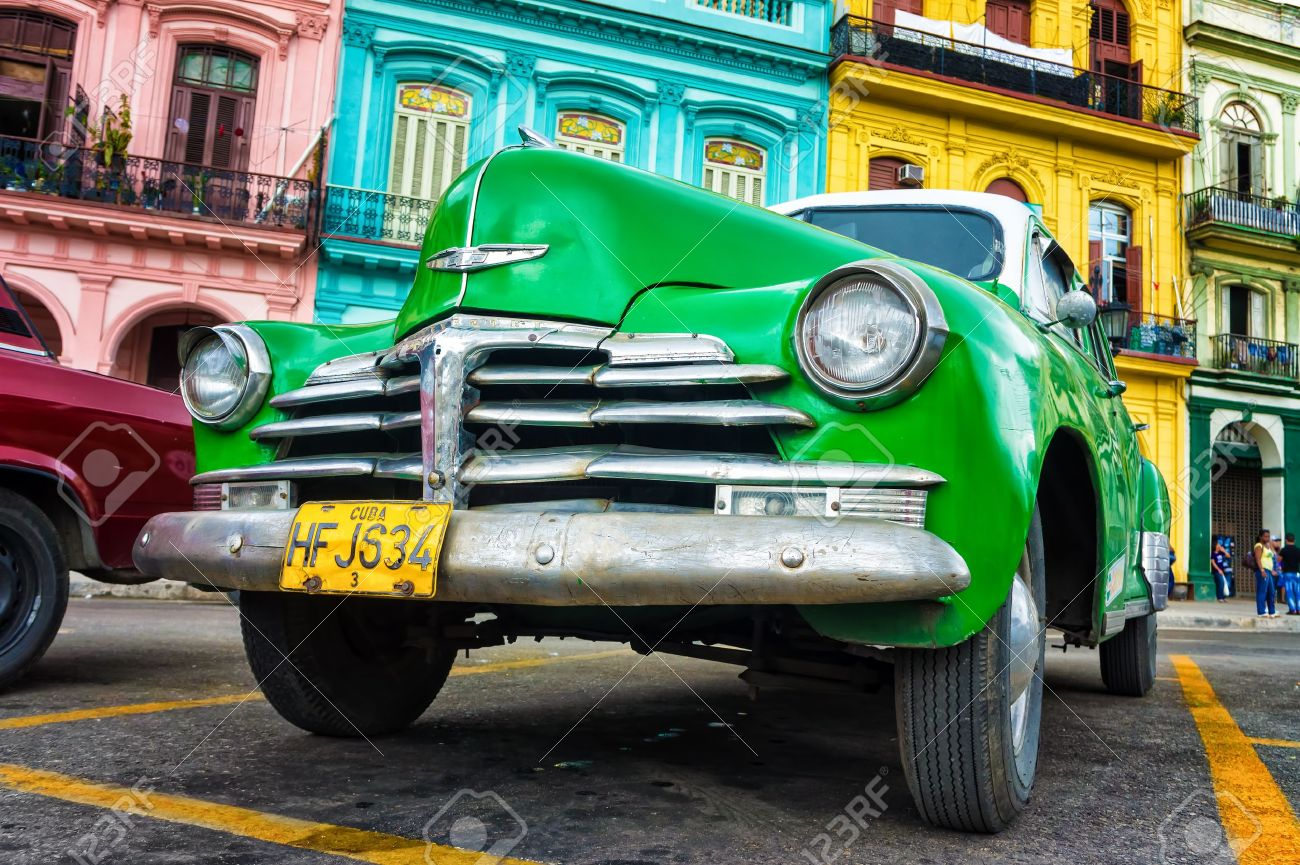 Old Chevrolet in front of colorful buildings in Havana Thousands