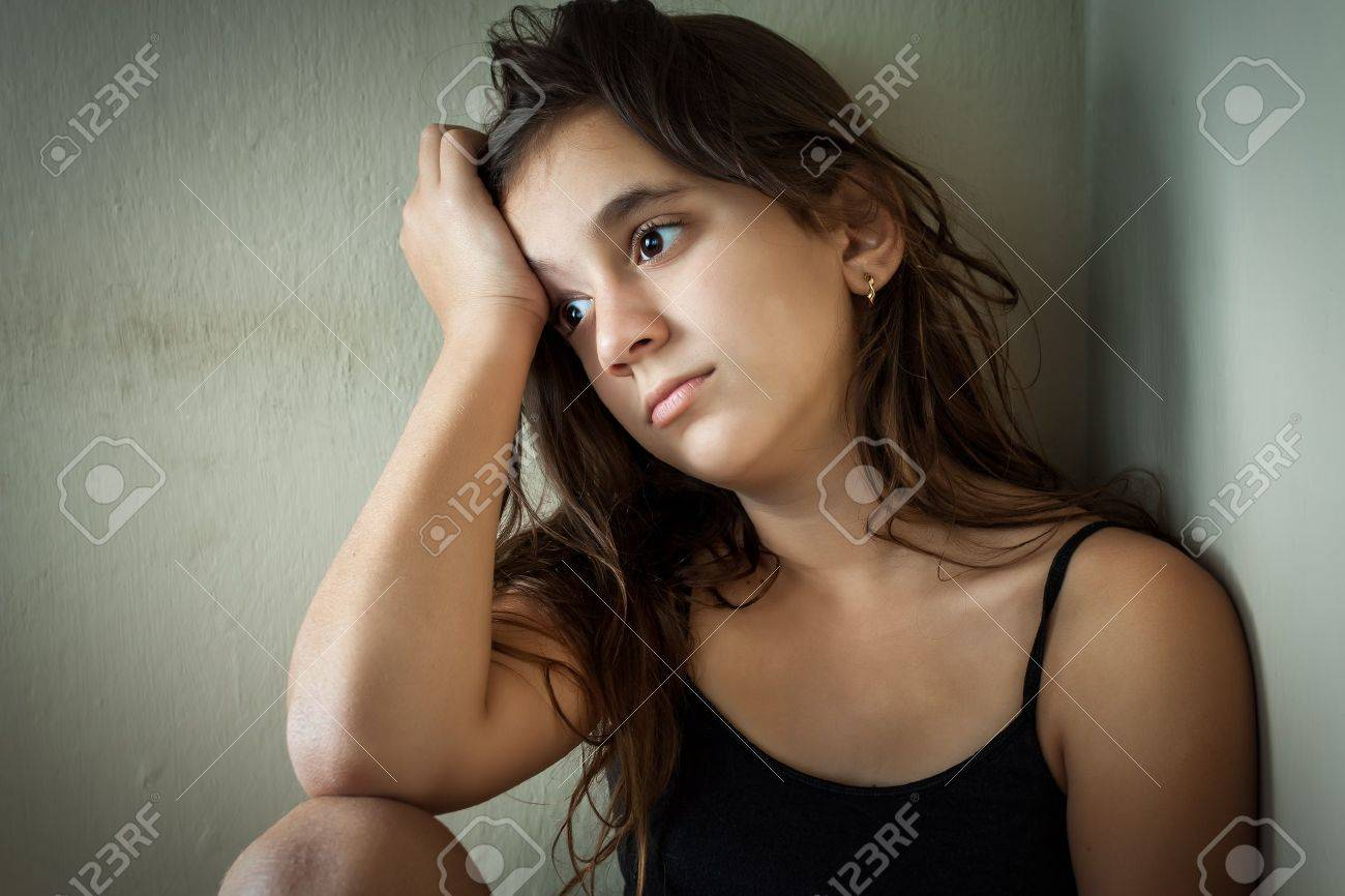Portrait of a sad hispanic girl sitting in a corner with a dirty wall background Stock Photo - 16695431