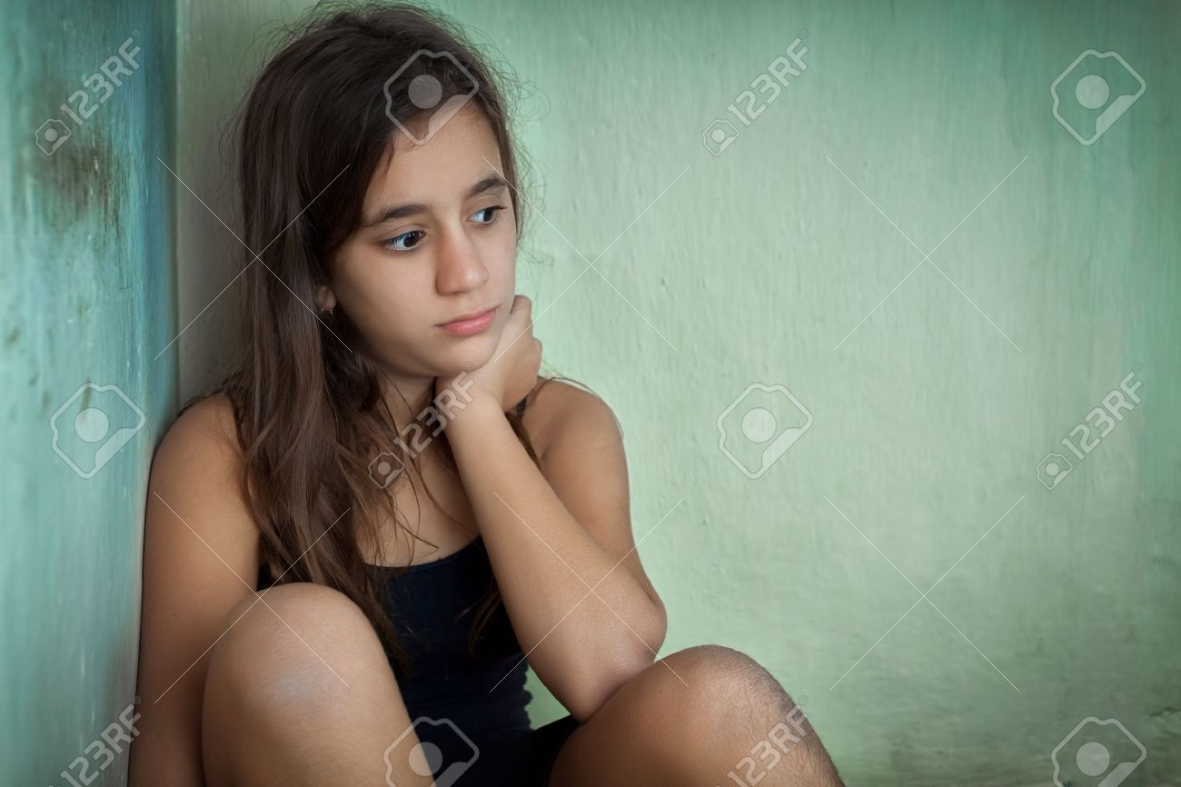 Sad and lonely hispanic girl sitting in the corner of a grungy house Stock Photo - 16733829