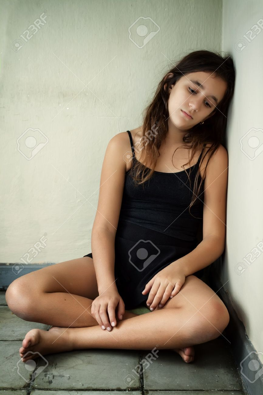 Depressed girl with a sad expression sitting in a corner Stock Photo - 16795221