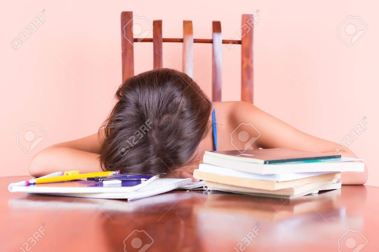 Exhausted student  sleeping with her head on a table and books by her side Stock Photo - 20179370