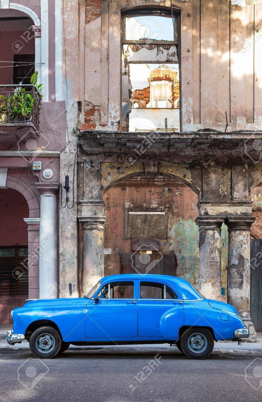 Old car next to crumbling decaying buildings on June 21, 2013 in Havana Stock Photo - 20449605