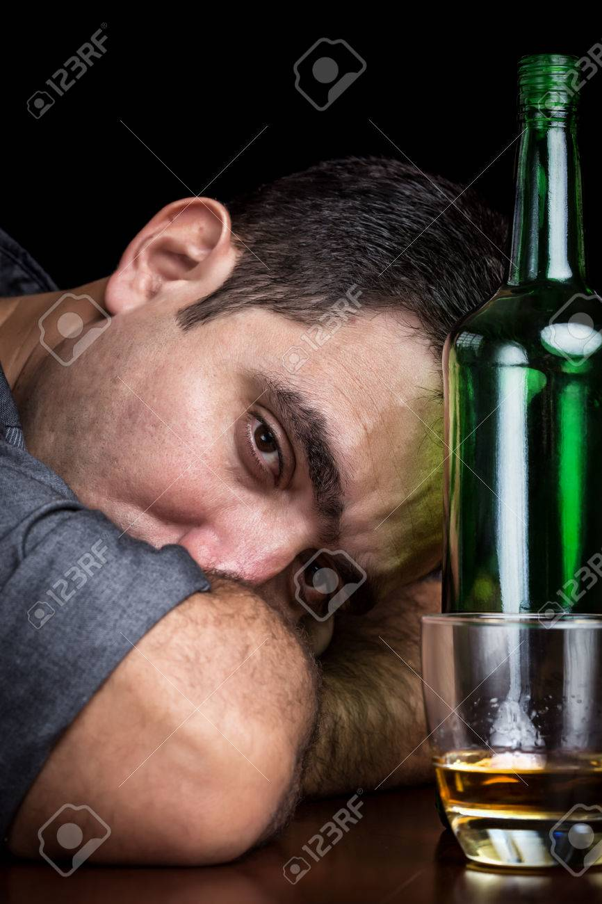 Drunk and depressed man with a sad face drinking alone  dark and dramatic image Stock Photo - 25013630
