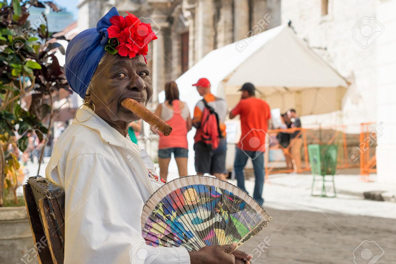 Anciana negro fumando un enorme puro cubano junto a la catedral de la habana Personajes como este son una vista común en las calles de La Habana Vieja Foto de archivo - 25655629