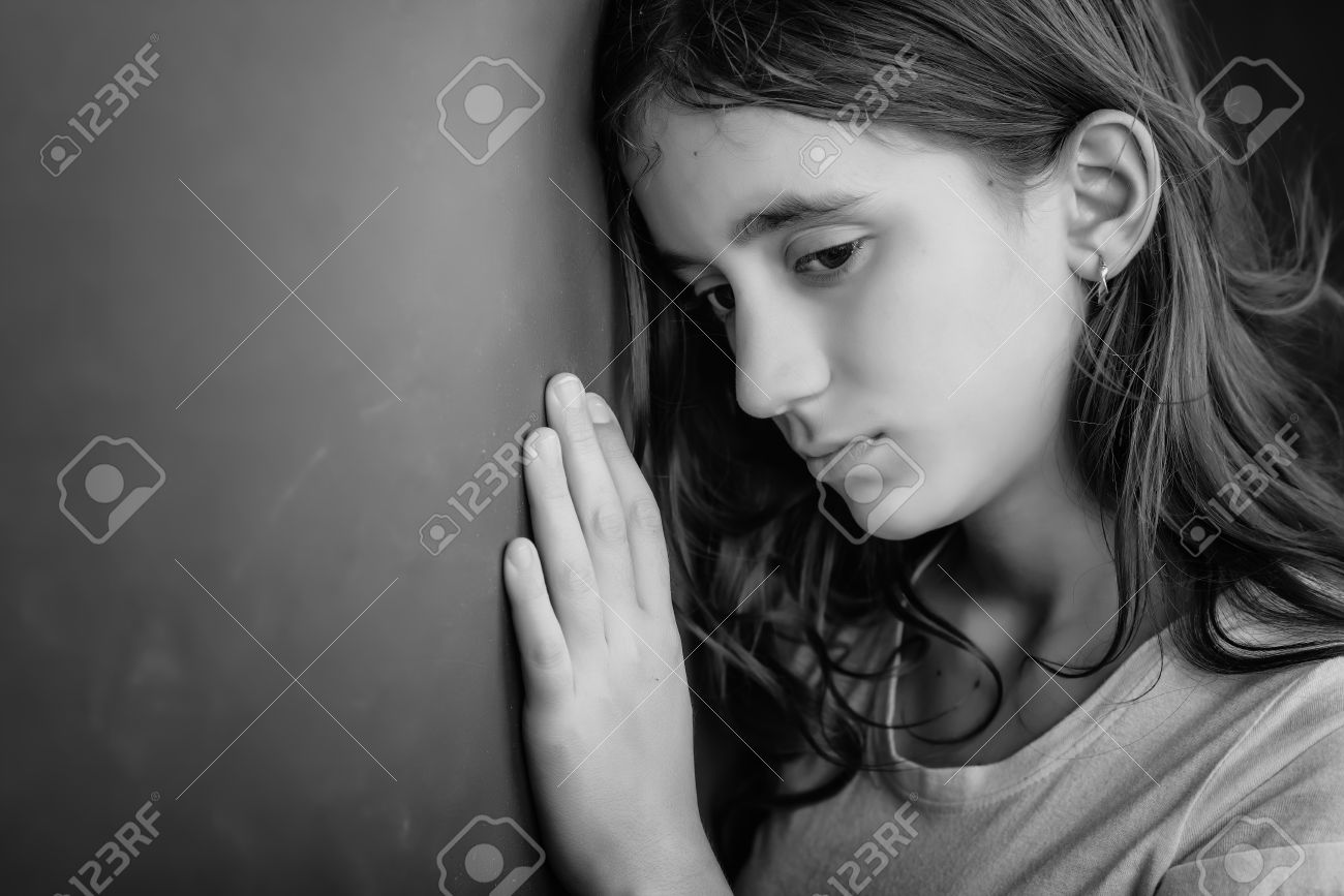 Grunge black and white portrait of a sad girl leaning against a wall stock photo