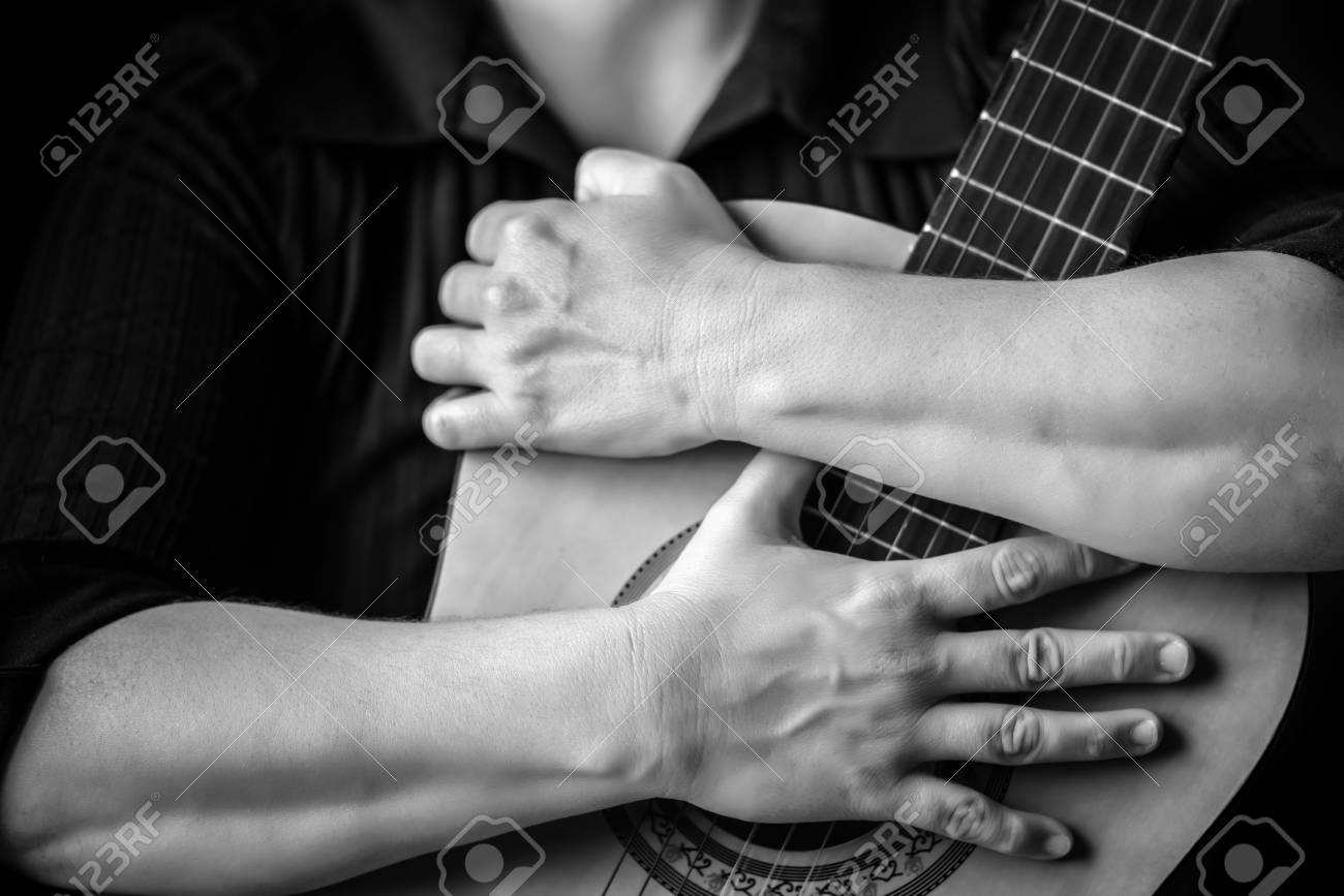 Hands Hugging An Acoustic Guitar In Black And White Stock Photo