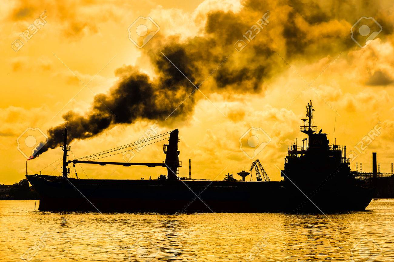 Oil refinery releasing a huge smoke column polluting the air with the silhouette of a ship on the foreground - 40298177