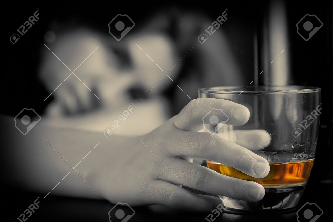 Drunk and depressed lonely woman holding a glass of whisky with a sad expression - 54766792