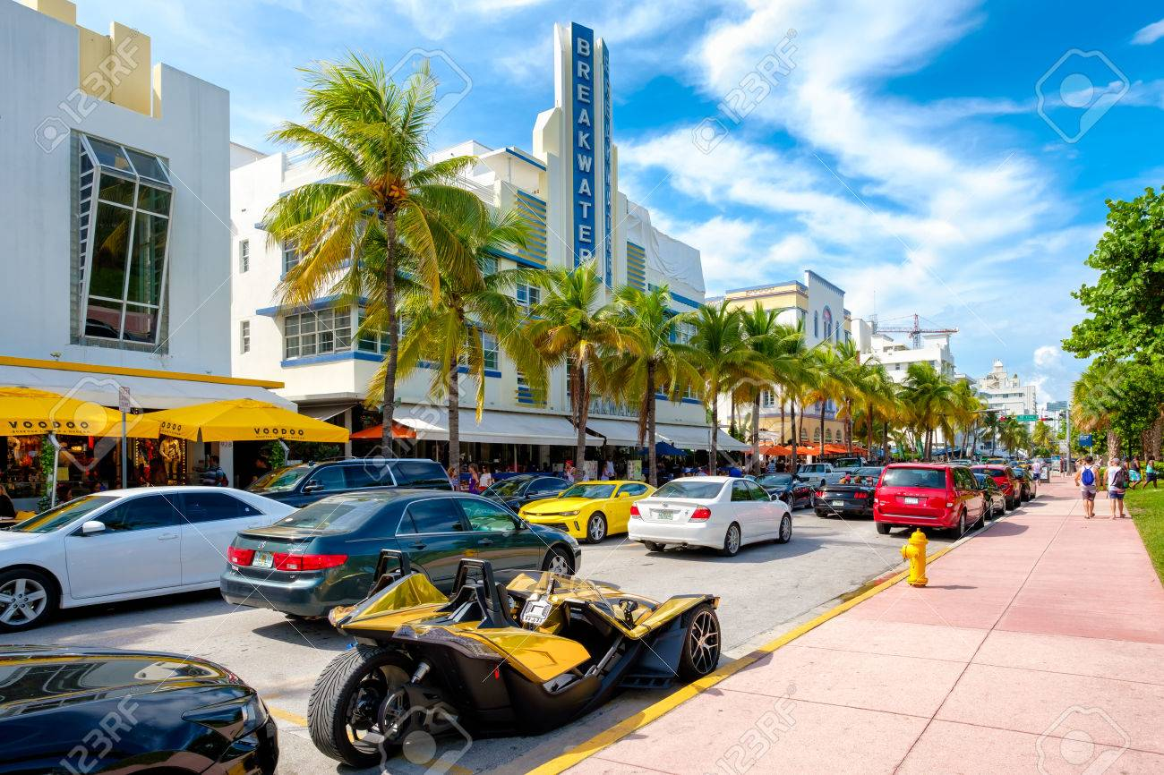 tourists and luxury cars at ocean drive a popular tourist