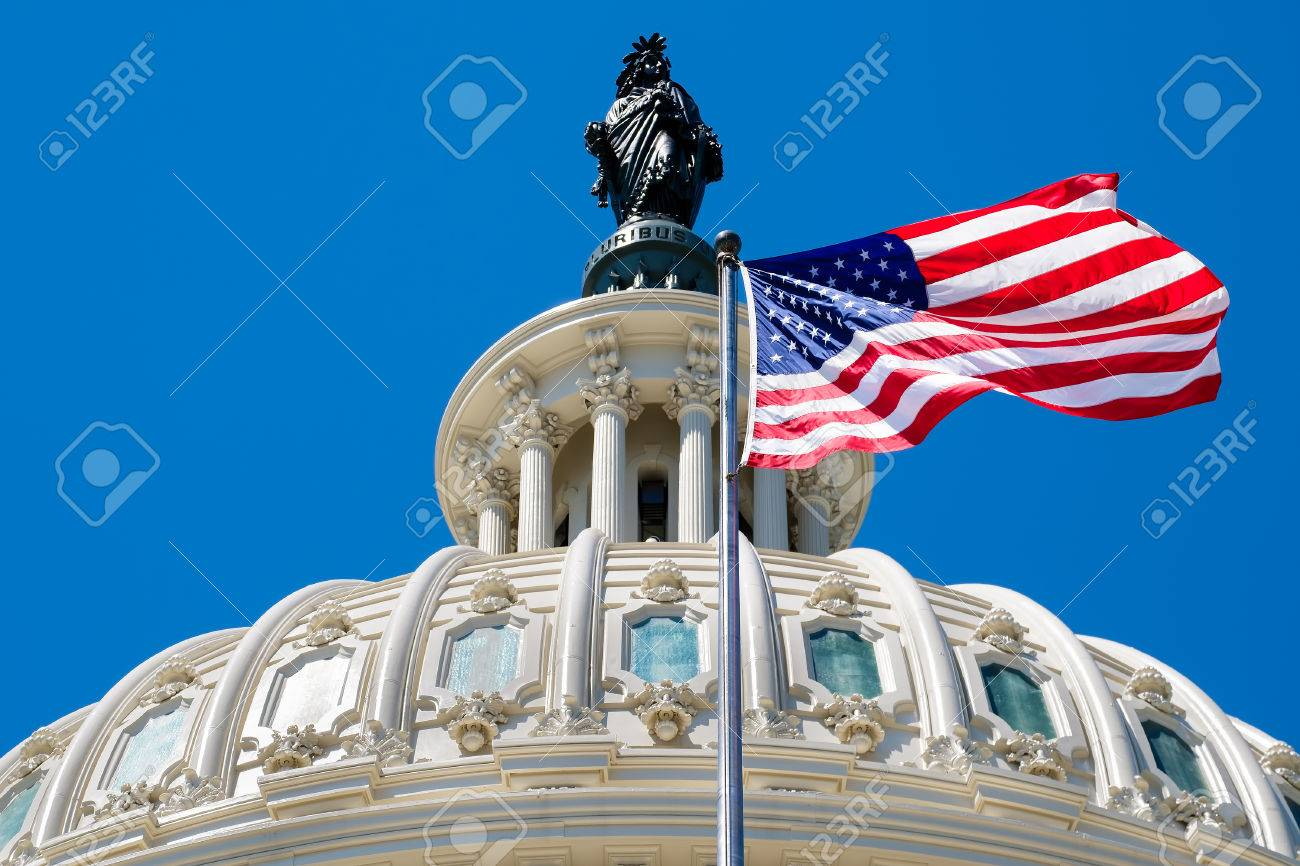 The United States flag waving in front of the Capitol dome in Washington D.C. - 62647111