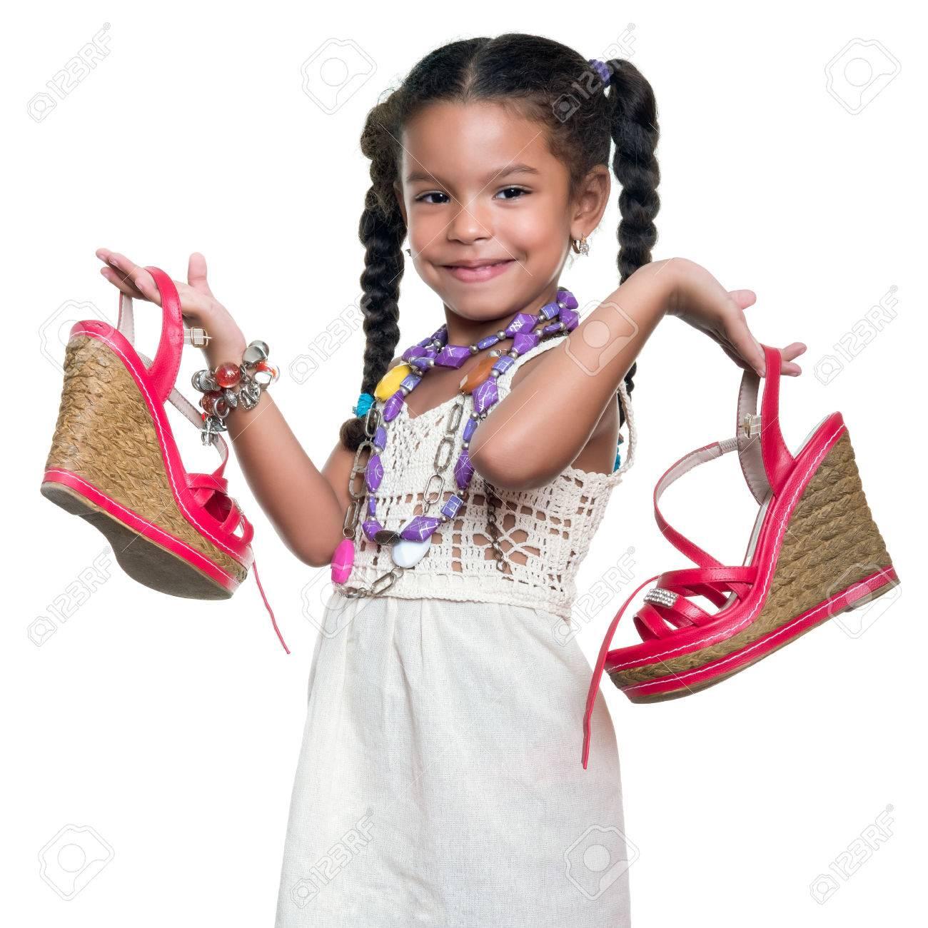 cc089df3ff9e1 Foto de archivo - Linda afroamericano pequeña niña vestida como una mujer  adulta con collares coloful que llevan un par de zapatos rojos - aislados  en ...