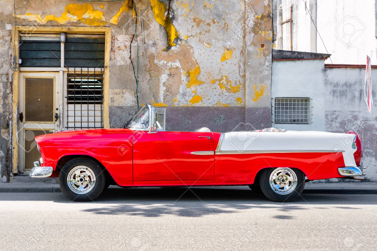 Classic red convertible car next to a shabby building in Old Havana - 68751654