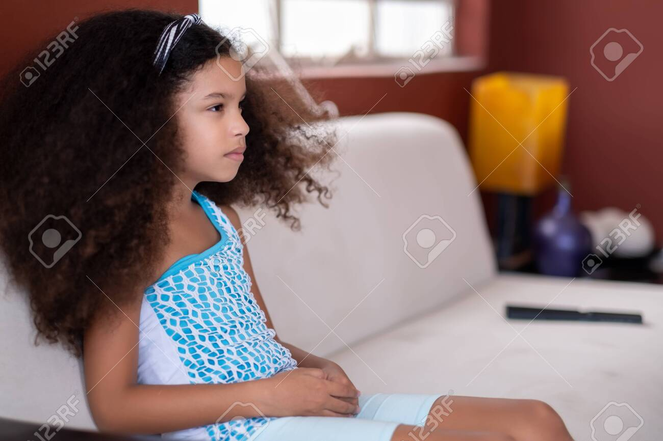 Cute multiracial small girl with beautiful curly hair watching TV at home - 150070086