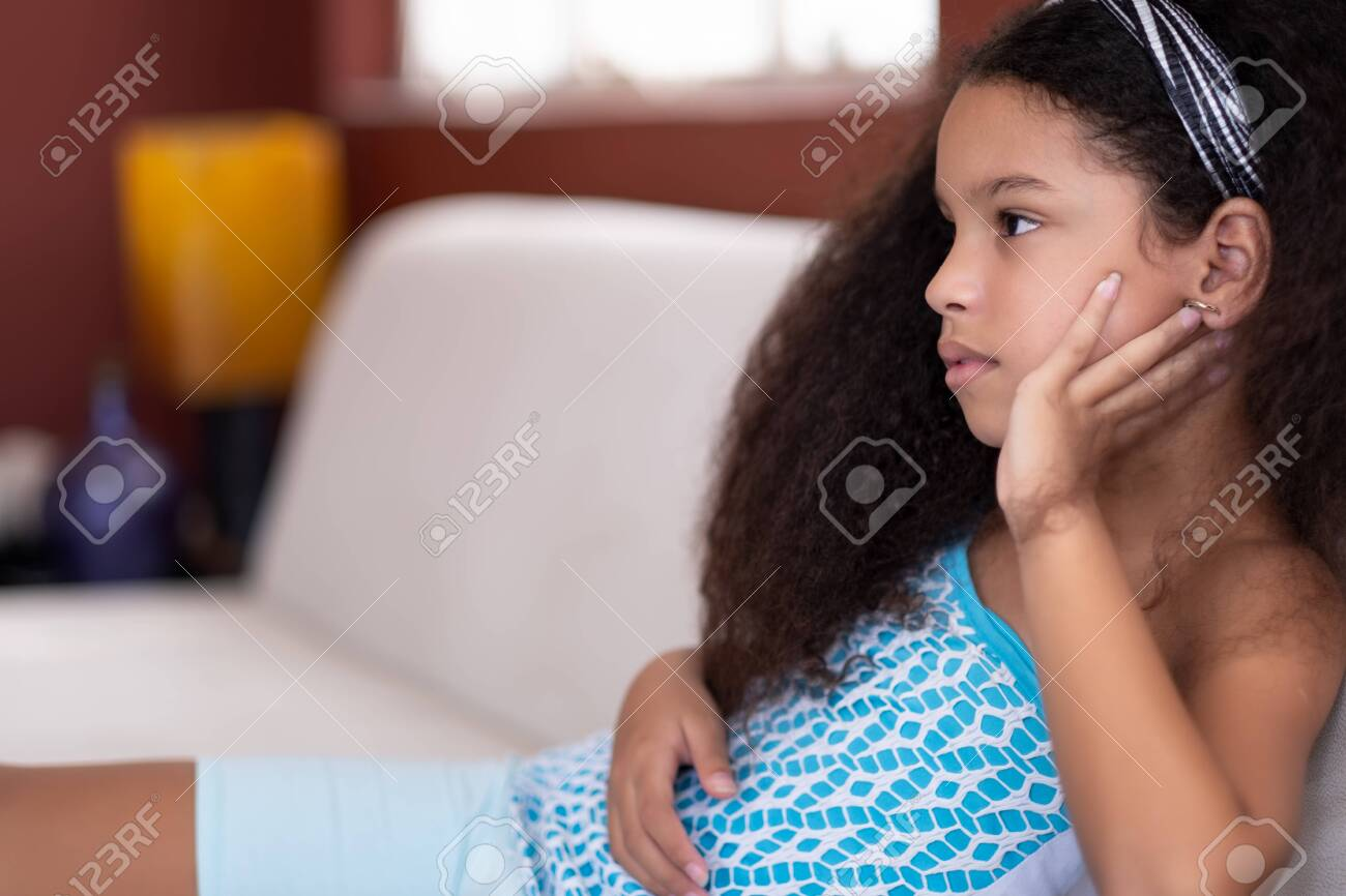 Cute multiracial small girl with beautiful curly hair watching TV at home - 150070130