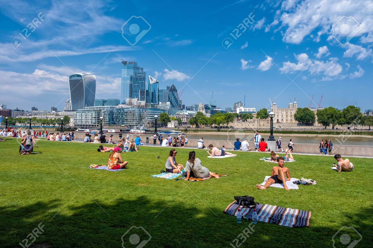 People enjoying summer near Tower Bridge in London with a view of the City skyline - 150065097