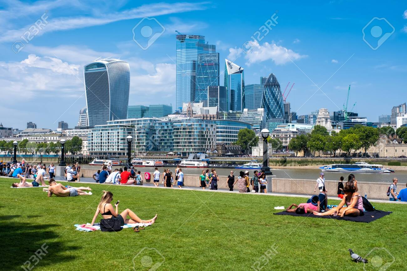 People enjoying summer near Tower Bridge in London with a view of the City skyline - 150065053