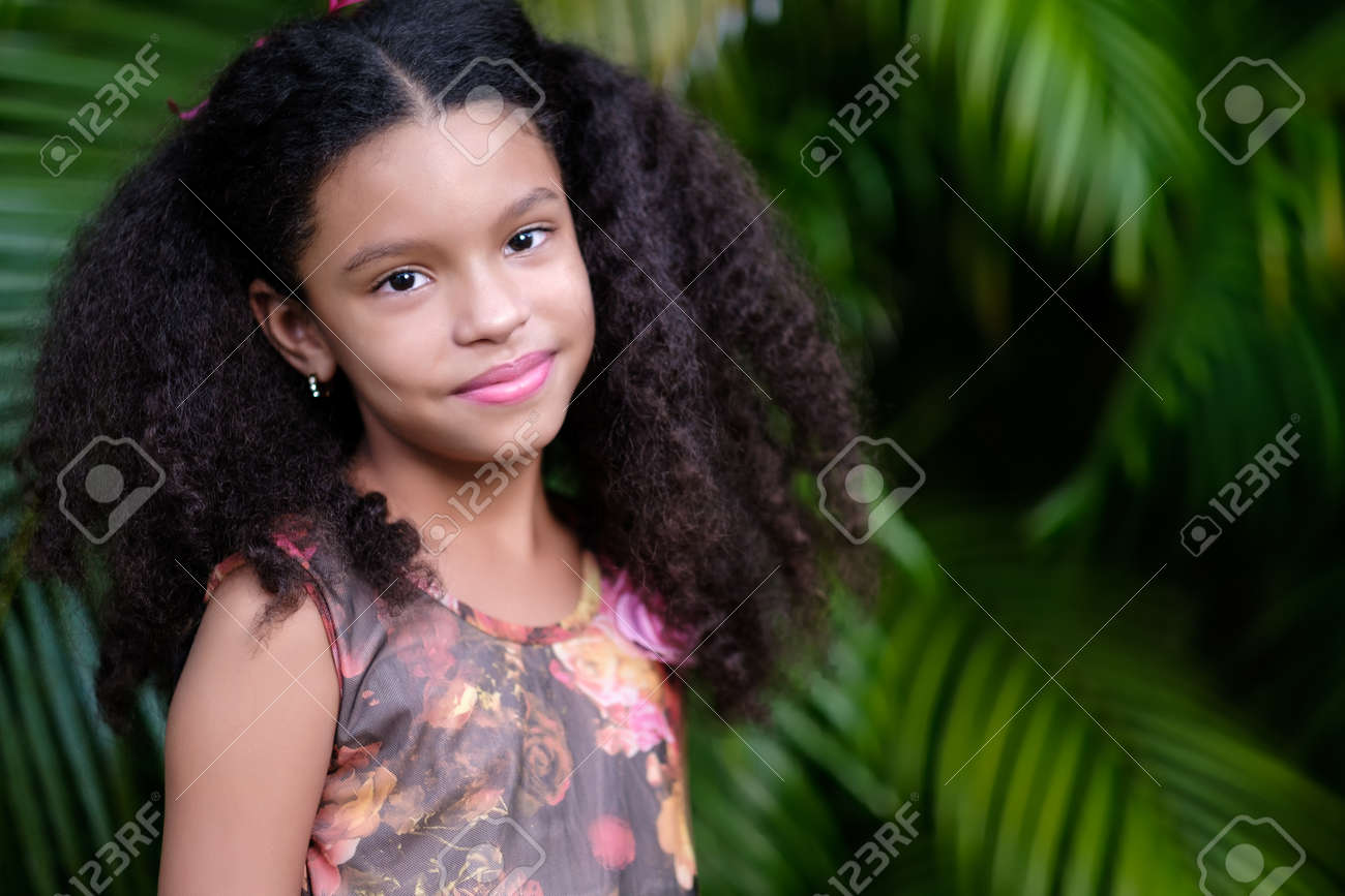 Portrait of a cute multiracial small girl with a green vegetation background - 159499002