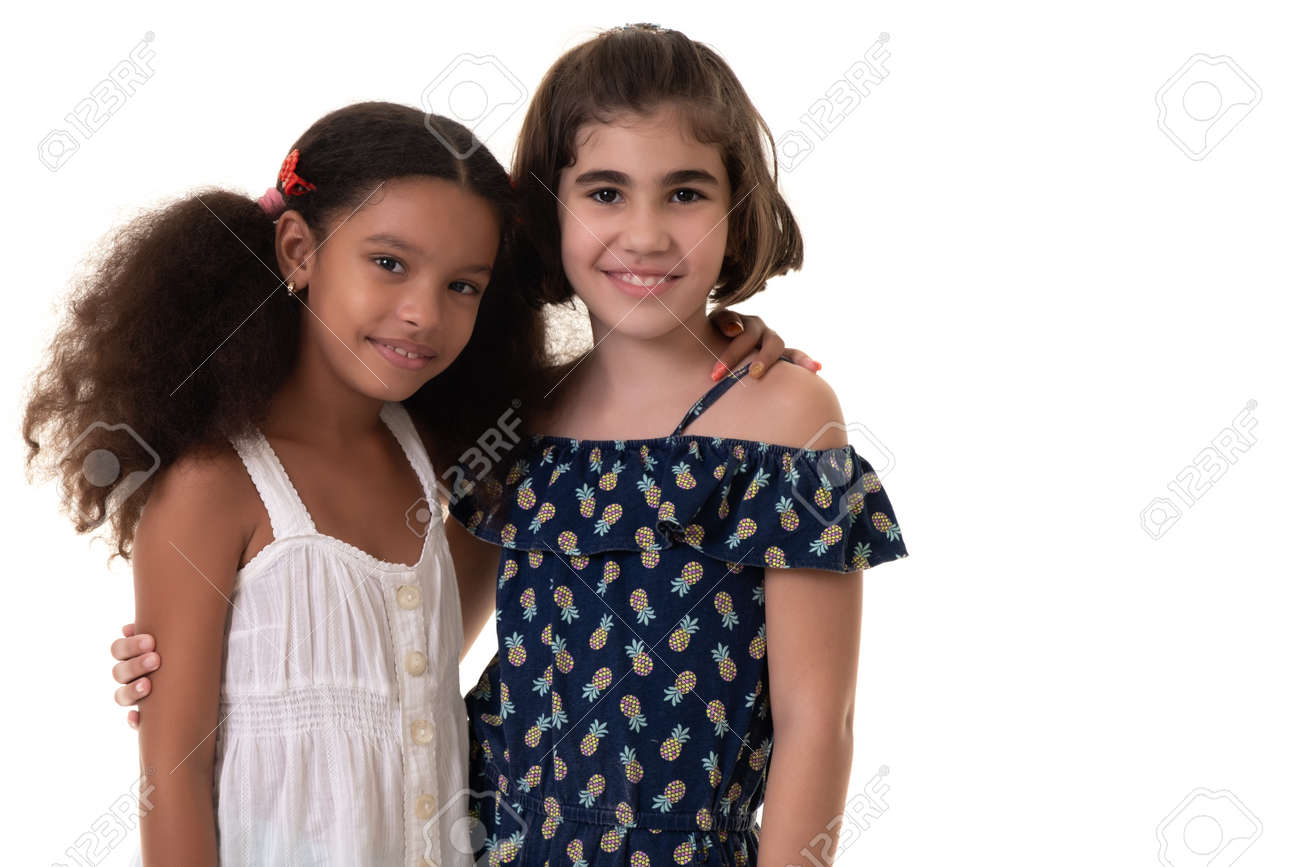 Two friendly small girls hugging - Hispanic and african-american - Isolated on white - 163555149