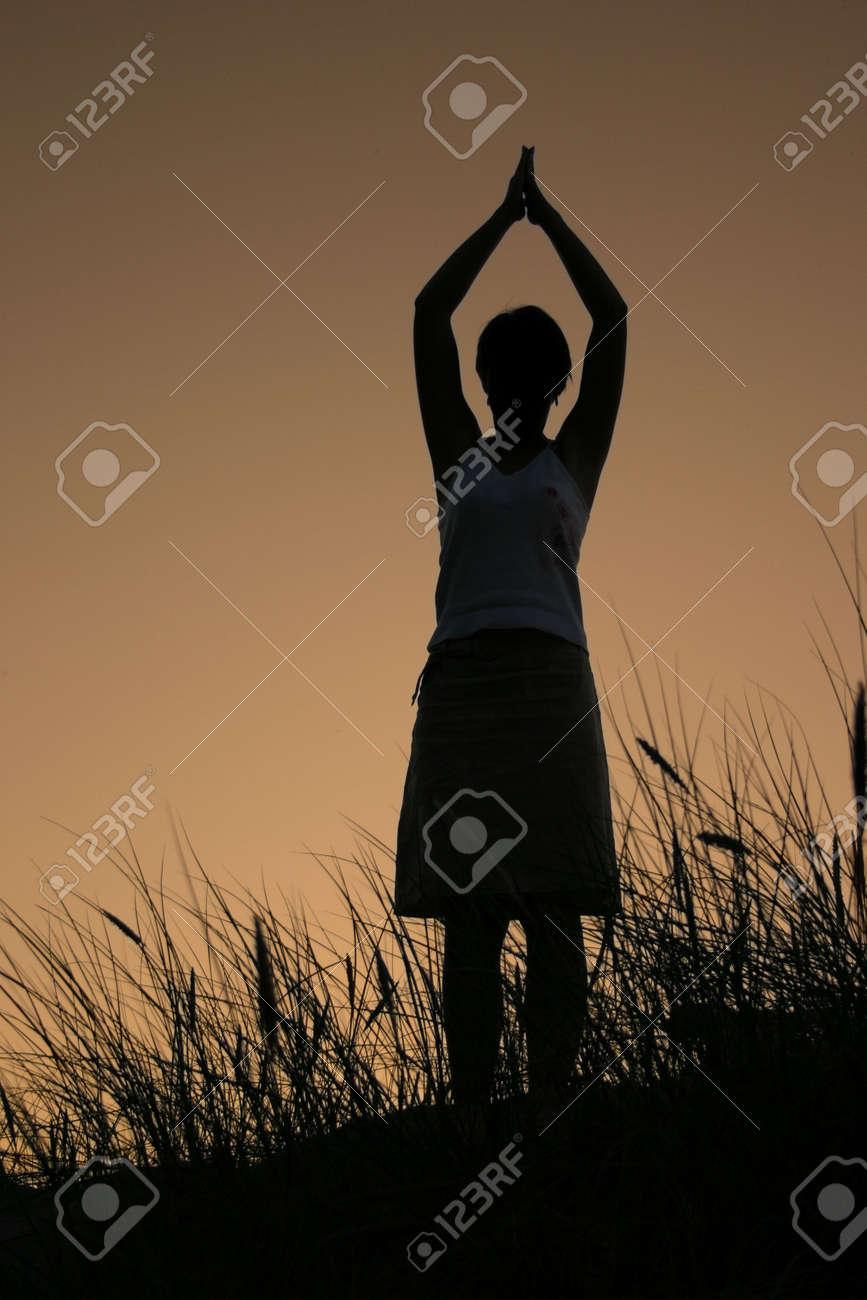 female silhouette celebrating summer sunset, PERSON ISN'T IDENTIFABLE Stock Photo - 667356