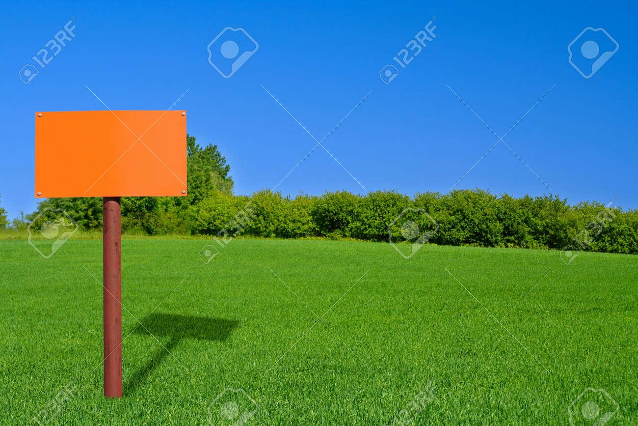 orange sign post on beautiful green meadow Stock Photo - 900278
