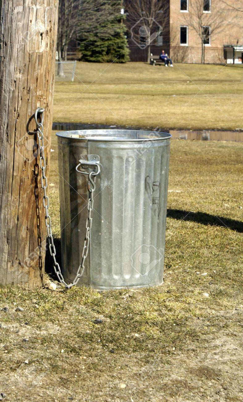 a metal trash can chained to a tree in a park stock photo