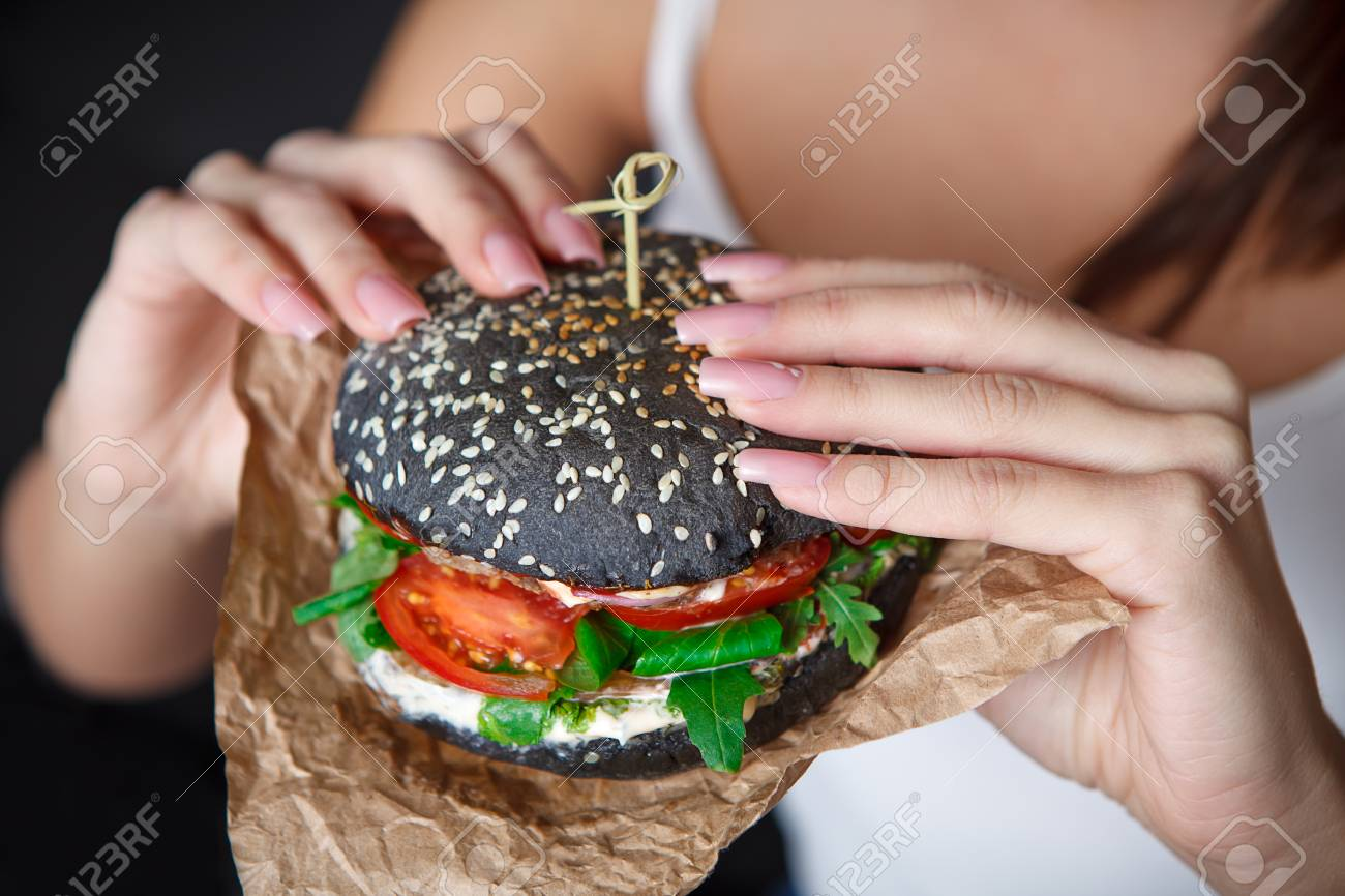 Close-up Black Burger In The Woman Hands. Nail Design. Concept ...