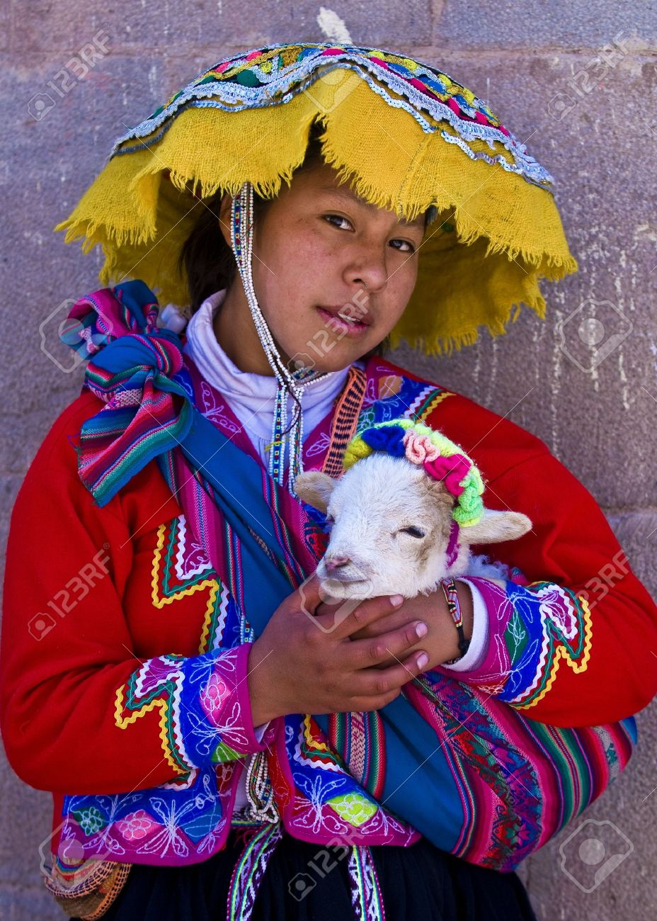 CUSCO , PERU - MAY 27 : Unidentified Peruvian girl in traditional colorful clothes holding a lamb in here arms in the  Stock Photo - 10582085