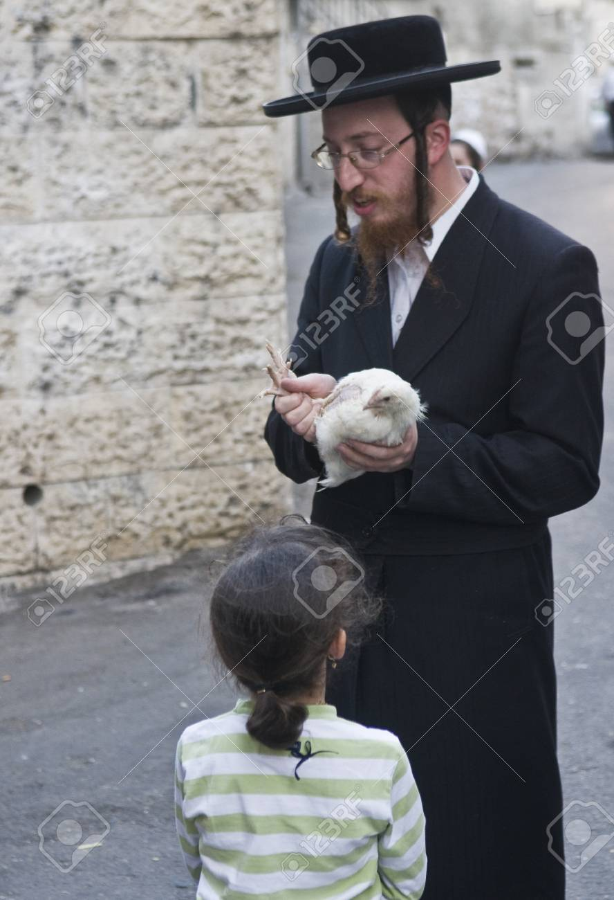 JERUSALEM - OCT 06 : An ultra Orthodox Jewish man waves a chicken over his daughter's head during the
