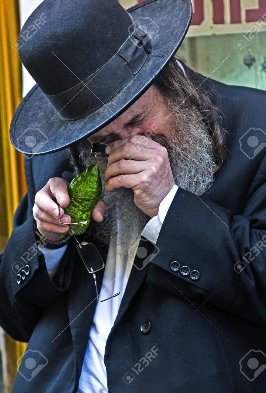 JERUSALEM - OCTOBER 10 2011 : An ultra-orthodox Jewish man inspects an Etrog Stock Photo - 10839152