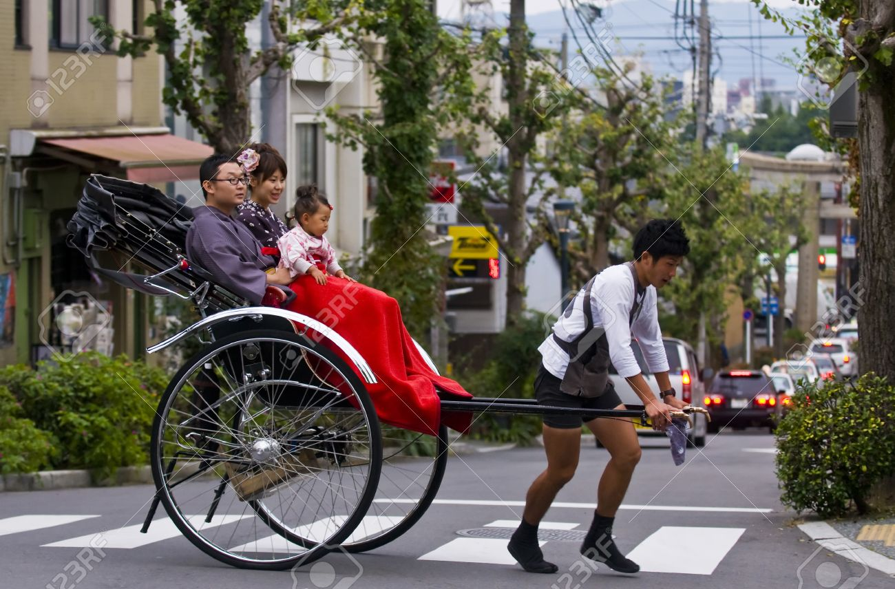 KYOTO , JAPAN - OCT 24 : Japanese family on a trditional rickshaw being pulled by a man on October 24 2009 in Kyoto , Japan - 11314555