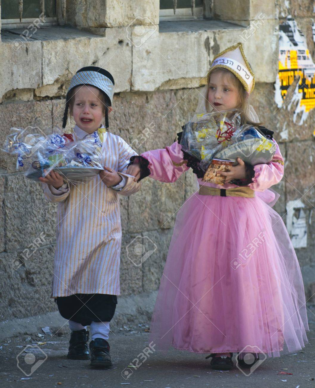 JERUSALEM - MARS 09 : Ultra Orthodox children holding Mishloach Manot during Purim in Mea Shearim Jerusalem on Mars 09 2012 , Mishloach Manot is traditional food gifts given during Purim Stock Photo - 12618649