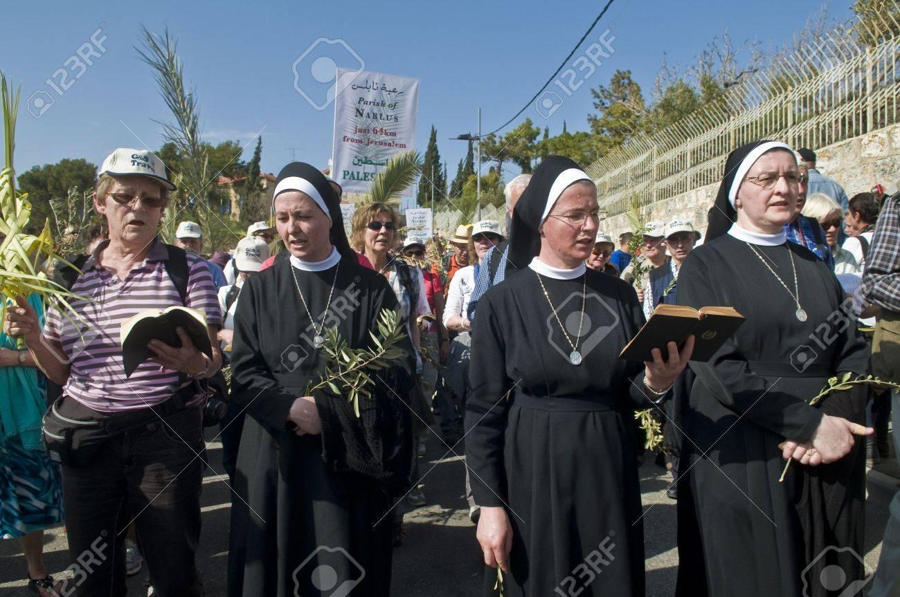 JERUSALEM - APRIL 01 : Unidentified nuns take part in the Palm sunday procession in Jerusalem on April 01 2012 , Palm sunday marks the beginning of the Holy week and Jesus christ's entrance into Jerusalem. - 13021423