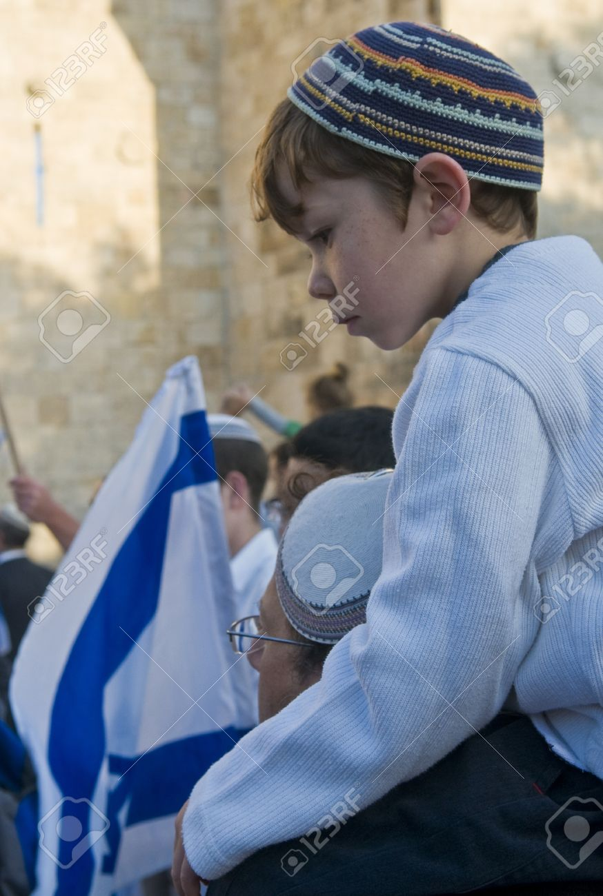 JERUSALEM - MAY 20 2012 : Right wing Israeli boy with his father on Jerusalem day in front of Damascus gate before marching throuh the Arab quarter of Jerusalem old city on May 20 2012 , Jerusalem day marks the anniversary of Israel capturing the eastern  Stock Photo - 13714878