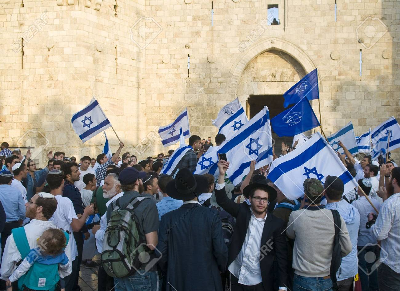JERUSALEM - MAY 20 2012 : Right wing Israeli men dance on Jerusalem day in front of Damascus gate before marching throuh the Arab quarter of Jerusalem old city on May 20 2012 , Jerusalem day marks the anniversary of Israel capturing the eastern part of th - 13714884