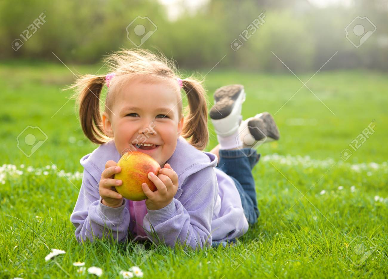 Little girl is laying on green meadow and going to eat a red apple Stock Photo - 9493757