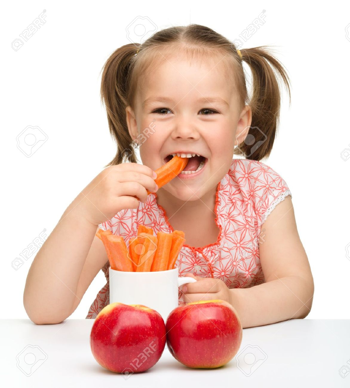 Cute little girl eats carrot and apples, isolated over white Stock Photo - 9557604