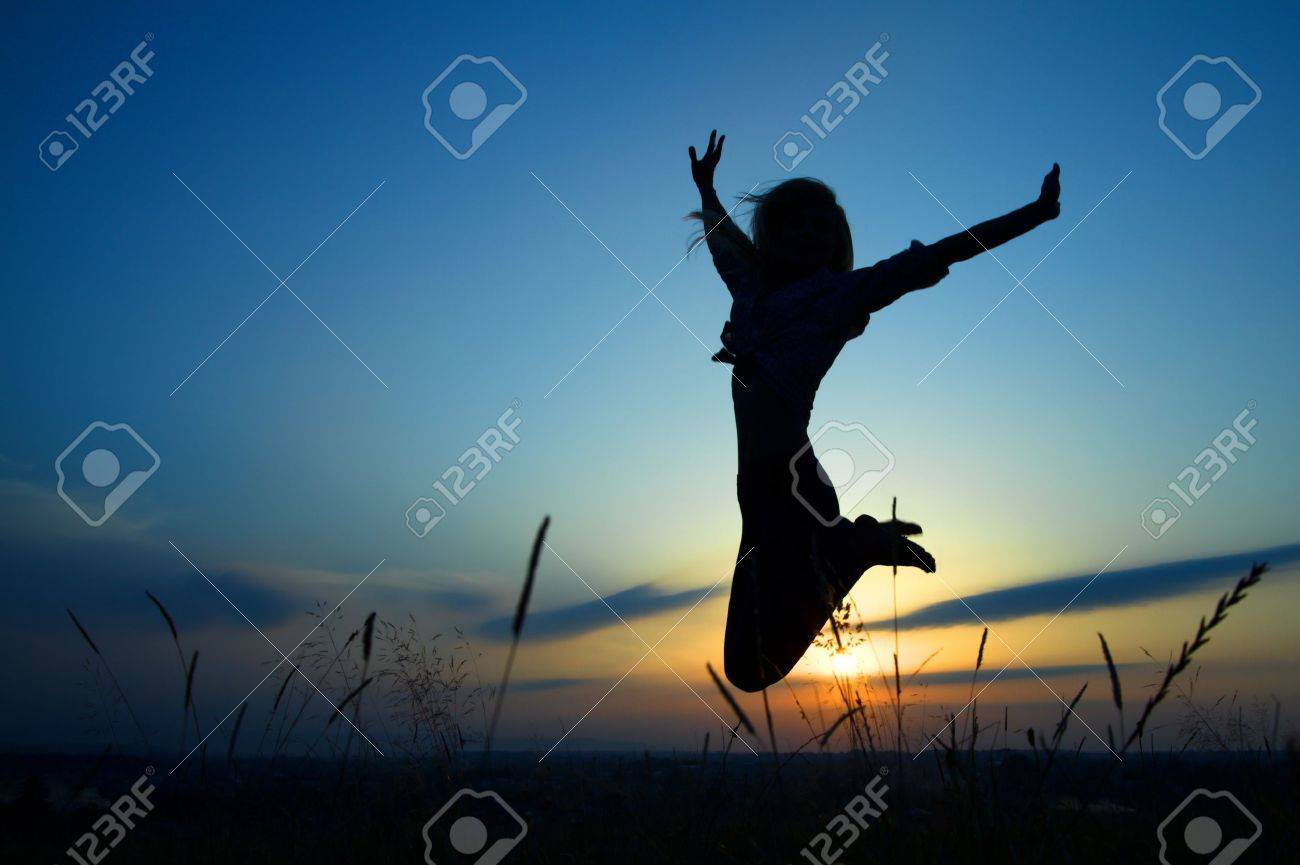 Silhouette of a beautiful girl jumping over sunset Stock Photo - 10528874
