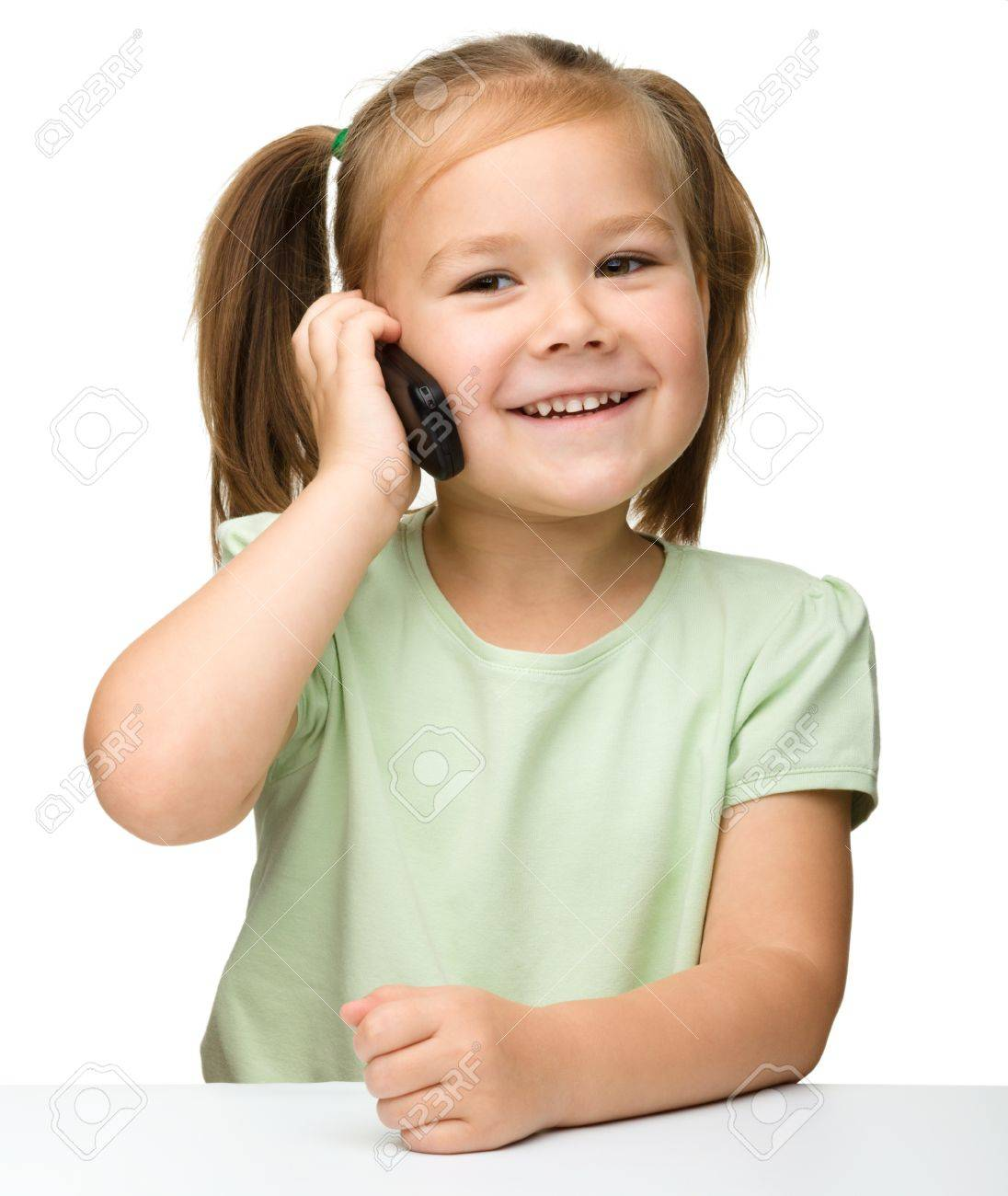 Cute little girl is talking on cell phone while sitting at table, isolated over white Stock Photo - 11555025